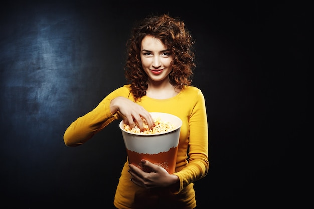 Beautiful sly woman grabs popcorn waiting for interesting movie