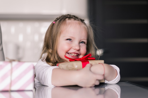 Beautiful small girl holding gifts on her lap and sitting in the kitchen