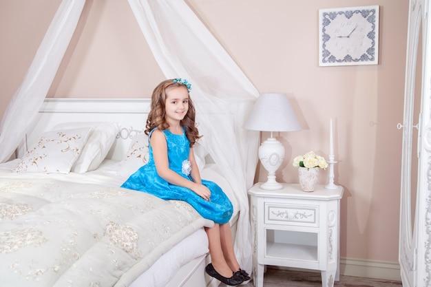Красивая маленькая девочка с голубым платьем и красивой прической сидит на кровати и смотрит в камеру с улыбкой. студийный снимок.