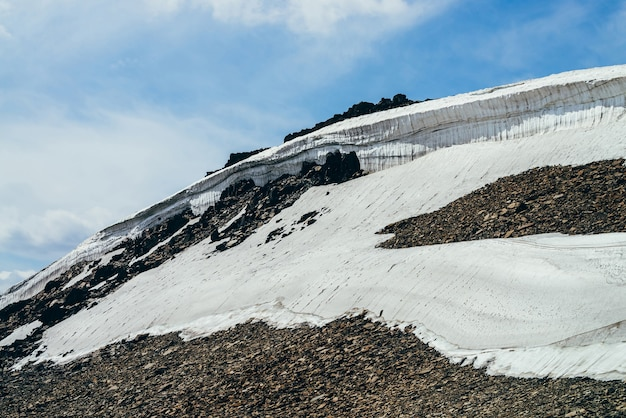 Beautiful small glacier with ice cornice on stony hill under cloudy sky