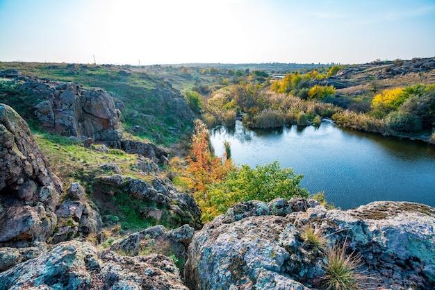 Красивая речка среди больших камней и зеленой растительности на холмах в украине