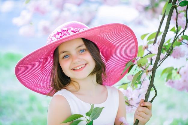 Beautiful small teen girl in pink fashionable hat with smiling face in spring flower blossom on sunny day spring teenager portrait