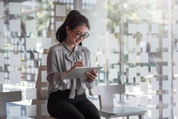 사무실에 앉아 그의 의자에 태블릿에 메모를 복용 아름 다운 스마트 아시아 비즈니스 여자. 면접을 기다리는 아시아 여자.