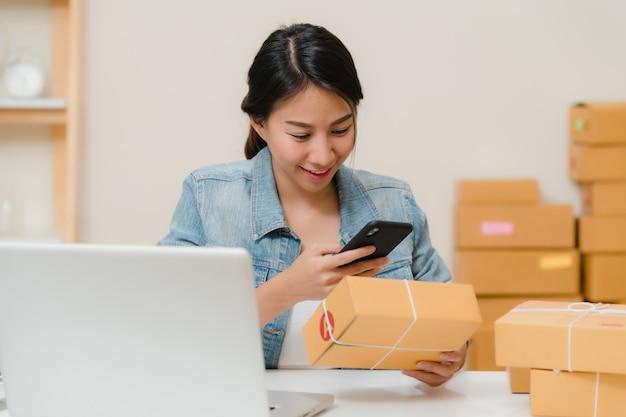 在宅勤務株式スキャンqrコードで製品をチェック中小企業の美しいスマートアジアの若い起業家ビジネス女性の所有者。