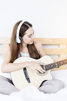 Beautiful smart caucasuan girl playing music on the bed with happiness and guitar