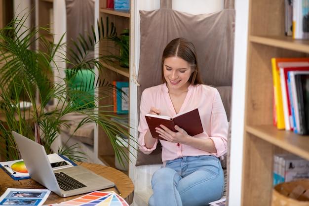 Красивая умная девушка, улыбаясь, делая заметки карандашом в блокноте