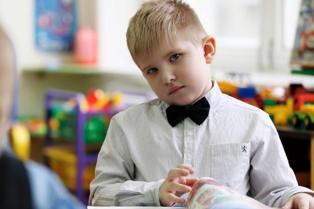 책을 들고 탁자에 앉아 있는 아름다운 똑똑한 소년. 책을 들고 있는 초등 학생