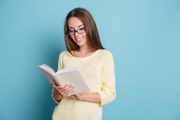 파란색 배경에 고립 된 책을 읽고 아름 다운 스마트 어린 소녀