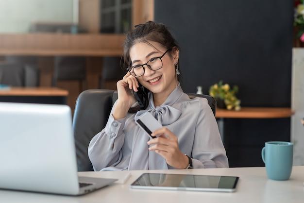 Красивая улыбка азиатская женщина разговаривает по мобильному телефону счастливой кредитной карты в офисе.