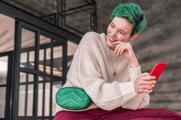 美しい笑顔。メッセージを読んで微笑むスタイリッシュなアクセサリーを身に着けた美しいファッションデザイナー