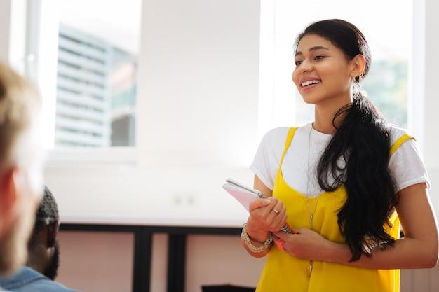 Прекрасная улыбка. веселая молодая красивая девушка держит свои заметки и улыбается, стоя у окна и принимая участие в семинаре