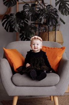 Beautiful smile little woman sits on a chair on a black dress at home. cute child with a wreath of flowers on head. the adorable child is less one year old.