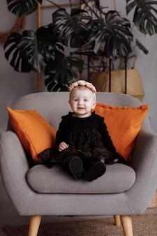 美しい笑顔の小さな女性が自宅の黒いドレスの椅子に座っています。頭の上の花の花輪を持つかわいい子。愛らしい子供は1歳未満です。