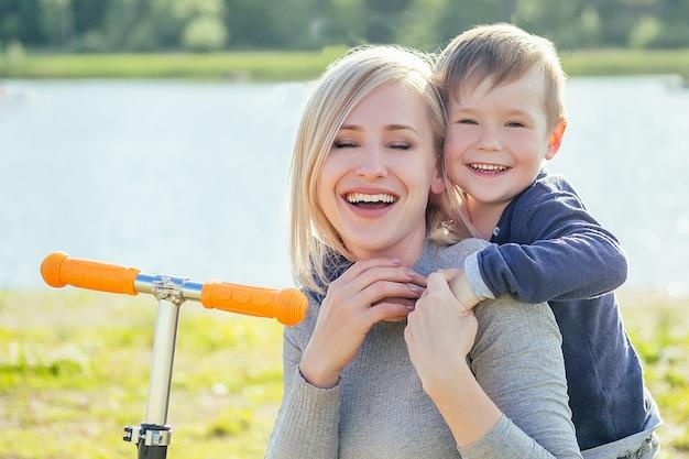 Красивая улыбка матери и ее милый маленький сын, сидящие на траве рядом со скутером, обнимаются в парке на фоне зеленых деревьев и речного озера