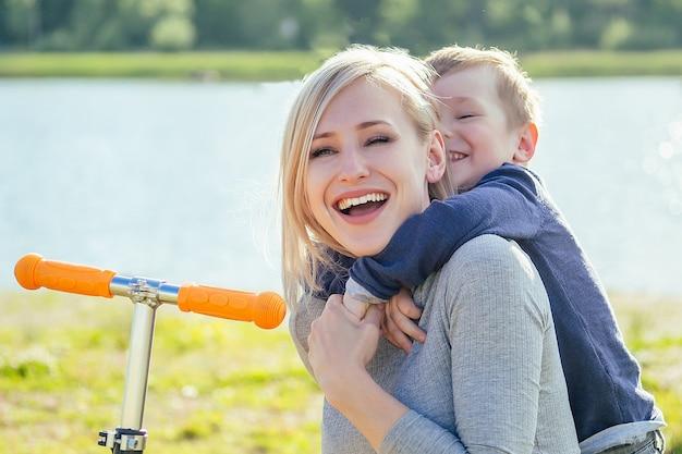 Красивая улыбка матери и ее милый ребенок (сын) сидят на траве рядом с самокатом в парке на фоне зеленых деревьев и реки
