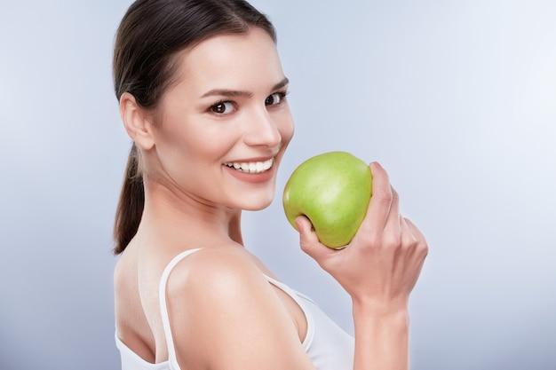 美しい笑顔、白い強い歯。青リンゴ、歯のケアを保持している真っ白な笑顔の若い女性の頭と肩。少し脇を向いた