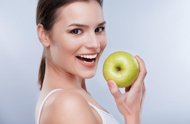 美しい笑顔、白い強い歯。青リンゴを持って真っ白な笑顔の若い女性の頭と肩は、少し脇を向いて、噛む準備ができて、クローズアップ