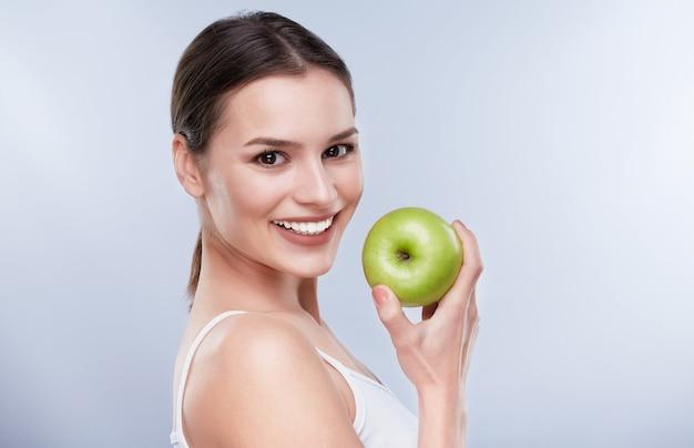 美しい笑顔、白い強い歯。青リンゴを持って真っ白な笑顔の若い女性の頭と肩が少し脇を向いた