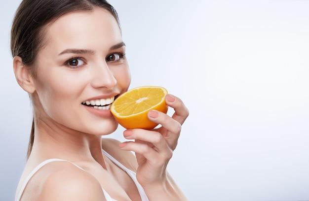 아름다운 미소, 하얀 강한 이빨. 노란 레몬의 절반을 들고 그것을 물고 백설 공주 미소로 젊은 여자의 머리와 어깨는 조금 옆으로 돌렸다, 근접 촬영
