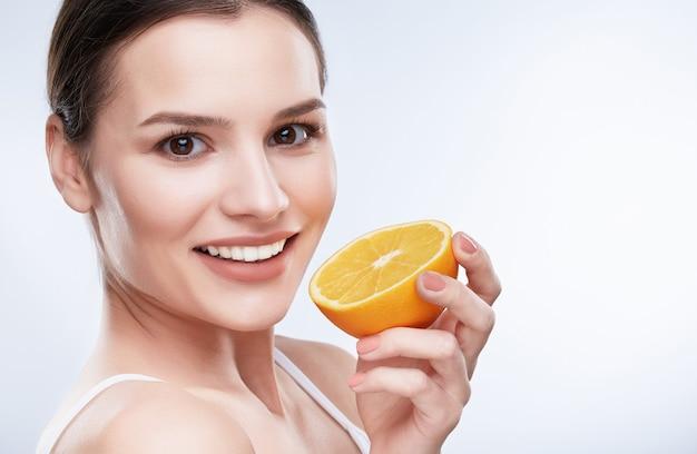 아름다운 미소, 하얀 강한 이빨. 노란색 레몬의 절반을 들고 백설 공주 미소로 젊은 여자의 머리와 어깨, 조금 옆으로 돌린 근접 촬영, 카메라를보고