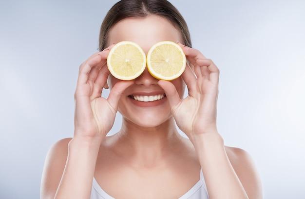 Красивая улыбка, белые крепкие зубы. голова и плечи молодой женщины с белоснежной улыбкой, держащей два желтых лимона возле глаз, закрытые глаза с лимонами