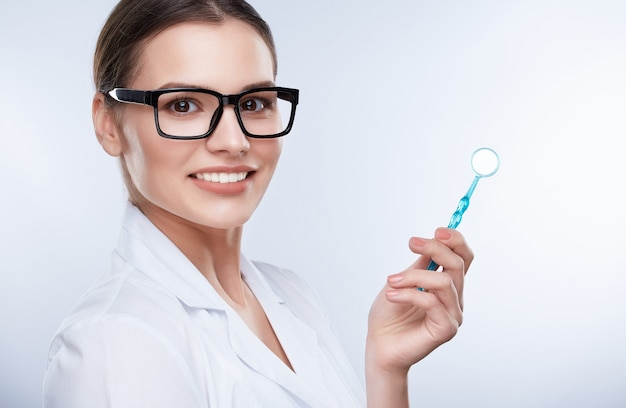 Beautiful smile, white strong teeth. head and shoulders of beautiful dentist in glasses with snow-white smile holding stomatological equipment, stomatological concept