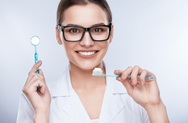 Beautiful smile, white strong teeth. head and shoulders of dentist in glasses with snow-white smile holding stomatological equipment and toothbrush, stomatological concept