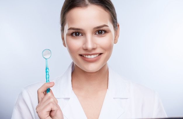 Beautiful smile, white strong teeth. head and shoulders of dentist with snow-white smile holding equipment for teethcare, stomatological concept, healthcare
