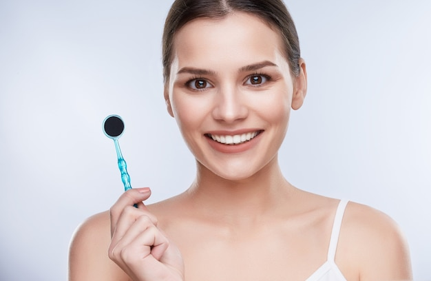 Beautiful smile, white strong teeth. head and shoulders of woman with snow-white smile holding equipment for teethcare, stomatological concept. healthcare, patient of dentist Premium Photo