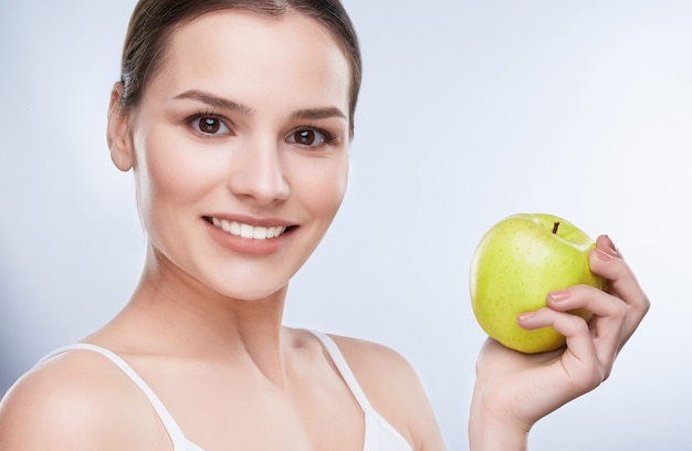 Beautiful smile, white strong teeth. head and shoulders of  woman with snow-white smile holding green, apple, turned a little bit aside, closeup