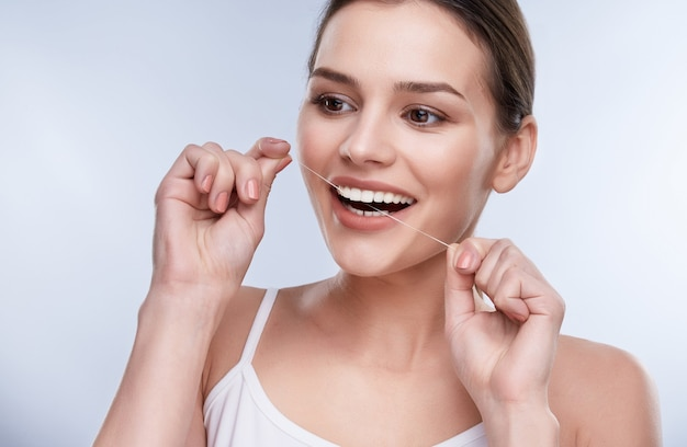 Beautiful smile, white strong teeth. head and shoulders of woman with snow-white smile holding tooth thread, stomatological concept. girl cleaning tooth with thread
