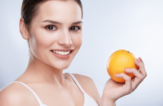 Beautiful smile, white strong teeth. head and shoulders of young woman with snow-white smile holding orange, turned a little bit aside, closeup