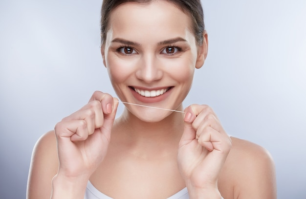 Beautiful smile, white strong teeth. head and shoulders of young woman with snow-white smile holding tooth thread, stomatological concept