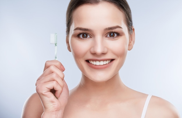 Beautiful smile, white strong teeth. head and shoulders of young woman with snow-white smile holding toothbrush, stomatological concept