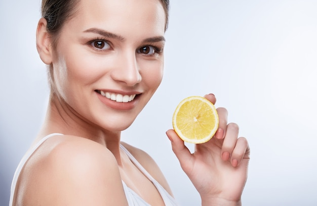 Beautiful smile, white strong teeth. head and shoulders of young woman with snow-white smile holding yellow lemon, turned a little bit aside, closeup
