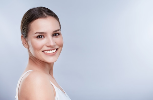 Beautiful smile, white strong teeth. head and shoulders of young woman with snow-white smile, teethcare, copyspace. turned a little bit aside