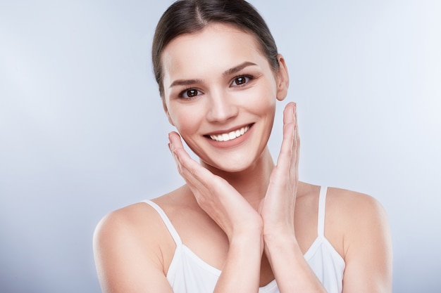 Beautiful smile, white strong teeth. head and shoulders of young woman with snow-white smile, teethcare. smiling woman, hands near face
