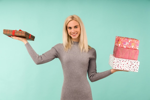 A beautiful smile woman in a gray dress, hold in hands gifts. celebration of christmas or new year on blue background