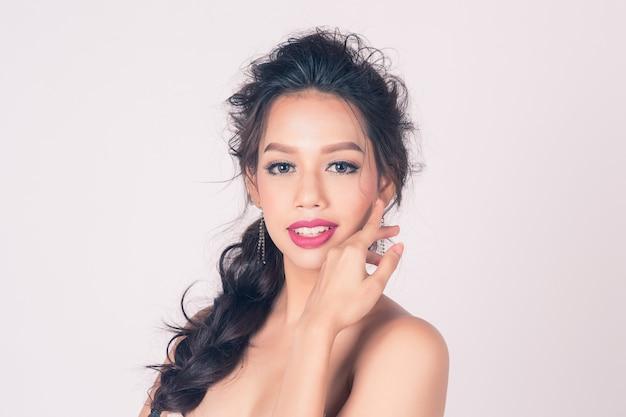 スキンケアや健康のための清潔で新鮮な肌と白い背景で補う美しい笑顔の女性