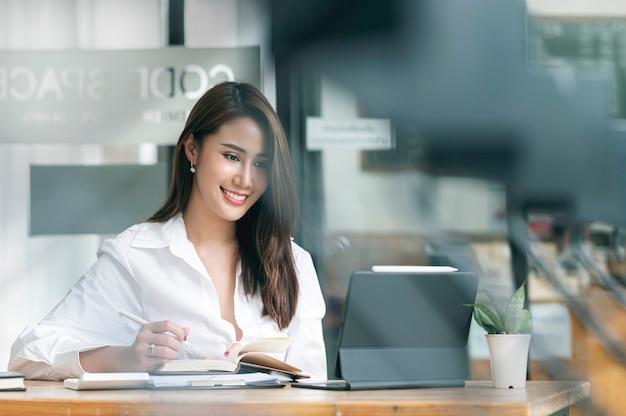 Красивый смайлик азиатский предприниматель работает на планшете компьютера и писать деловую заметку, сидя за столом в офисной комнате.