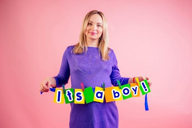 妊娠9ヶ月の美しい笑顔の妊娠中の大きなお腹の女性は、ピンクの背景にスタジオで「それは男の子です」と刻まれたカードを持っています。出産とベビーシャワーのコンセプトを待っています。