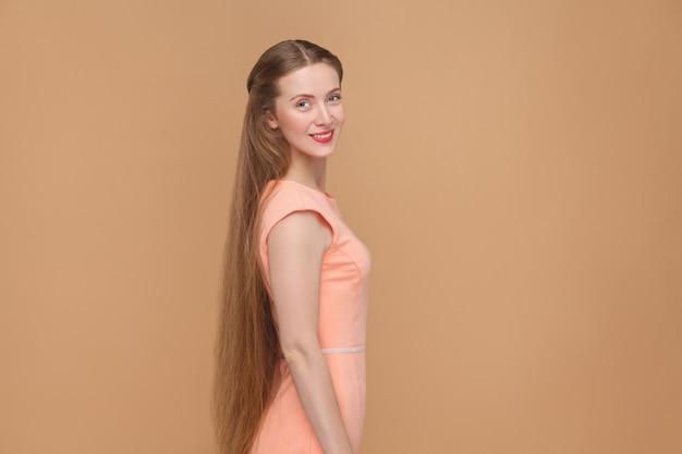 Красивый смайлик женщина с длинными каштановыми волосами, глядя на камеру. портрет эмоциональной милой красивой женщины с макияжем и длинными волосами в розовом платье. студийный снимок, изолированные на светло-коричневом или бежевом фоне