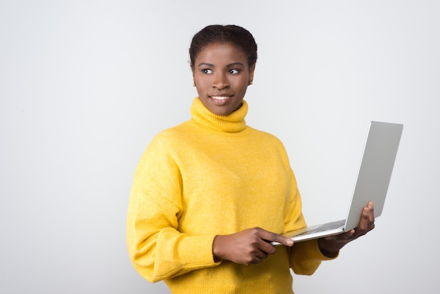 Beautiful smiling african american woman holding laptop