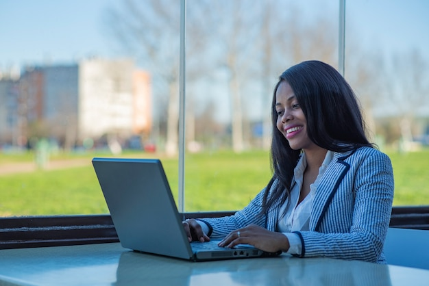 Beautiful smiling african-american woman using a laptop
