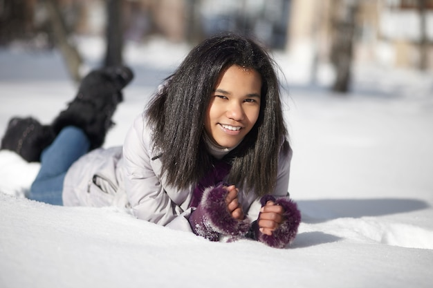 Beautiful smiling american black female lying in the snow outdoors