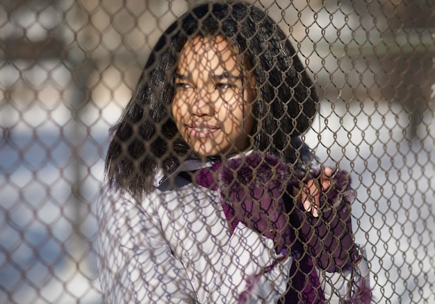 Beautiful smiling american female in the street outdoors behind grating