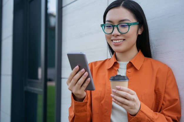 Beautiful smiling asian woman holding cup of coffee using mobile app shopping online