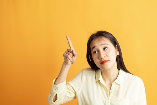 Красивейшая усмехаясь азиатская выставка женщины указывая рукой к пустому космосу в сторону на желтой предпосылке с космосом экземпляра.