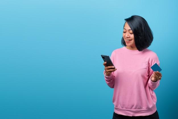 携帯電話を使用して青い背景にクレジットカードを保持している美しい笑顔のアジアの女性