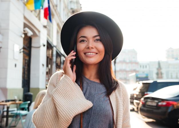 街の道を歩いて携帯電話で話している美しい笑顔のアジア女性